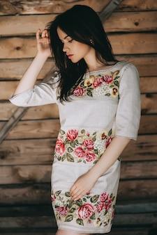 Jovem e linda vestindo roupas nacionais ucranianas em cabana de madeira