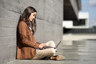 Jovem empresária sentada no chão olhando para o laptop. Mulher bonita com desgaste formal usando fones de ouvido.