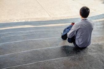 Jovem empresário bonito sentado na escada e usando seu smartphone (foco seletivo).