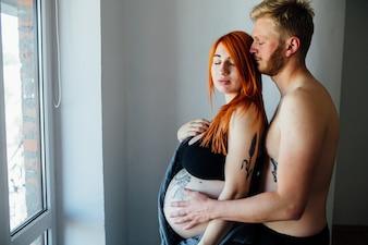 Jovem grávida abraçando em casa
