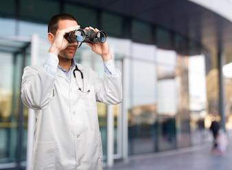 Jovem médico chocado usando um binóculo