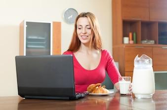Jovem, menina de cabelos vermelhos, em rosa usando o laptop durante o café da manhã em casa