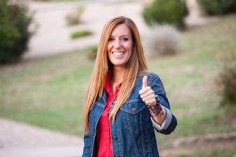 Jovem mulher dando polegar como sinal de sucesso.