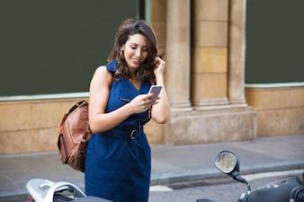 Jovem, mulher, lendo mensagem no telefone e sorrindo