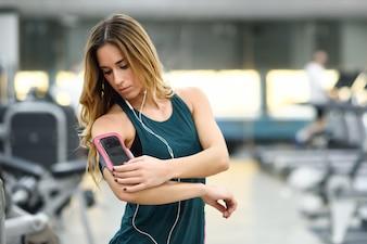 Jovem, mulher, usando, smartphone, ficar, ginásio