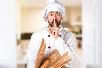 Jovem padaria segurando um pouco de pão e fazendo um gesto de silêncio na cozinha