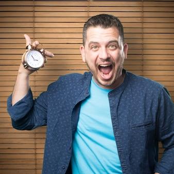 Jovem vestindo uma roupa azul. Segurando um relógio. Ele está gritando.