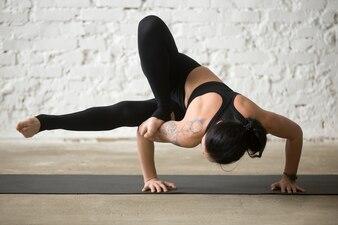Jovem yogi mulher atraente em Maksikanagasana pose, loft branco