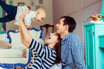 Jovens pais brincando com criança pequena
