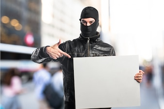 Ladrão segurando um cartaz vazio em fundo não focado
