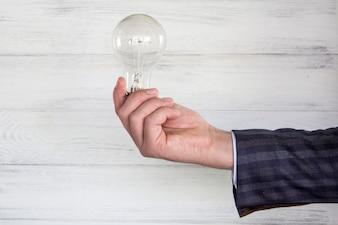 Lâmpada elétrica na mão do empresário.