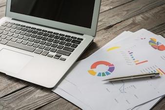 Laptop com documentos de negócios coloridos