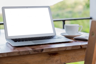 Laptop com tela em branco em uma mesa de madeira e uma chávena de café