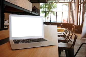 Laptop com tela em branco Mock-up na mesa de madeira em frente ao espaço do café coffeeshop para texto. montagem de exibição de produto - conceito de tecnologia