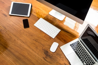 Laptop, computador e celular sobre uma mesa de madeira