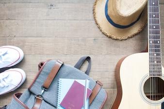 Layout plano criativo de conceito de viagem com passaporte, mochila, sapatos, chapéu de palha e guitarra no fundo de madeira