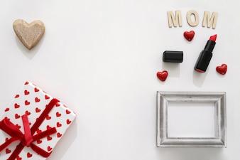 Letra da mamã, batom, quadro, caixa de presente e coração