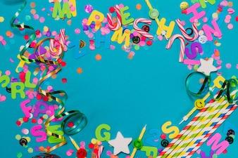 Letras, confetes e serpentina em uma tabela azul