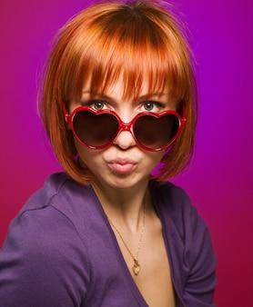 Linda garota vermelha com óculos de sol