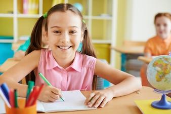 linda menina sorrindo em uma sala de aula
