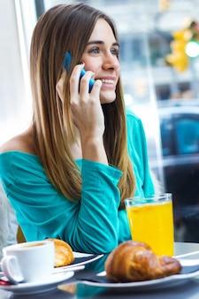 Linda mulher morena no café está falando por telefone celular
