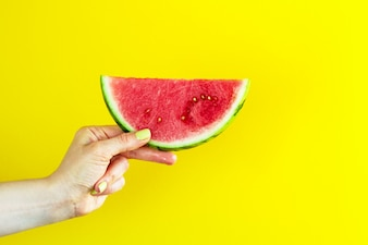 Lindas mãos femininas que mantêm deliciosa melancia apetitosa vermelha saborosa em fundo amarelo brilhante. Conceito de verão.