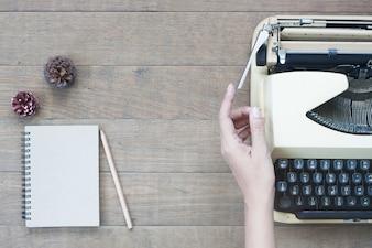 Liso plano criativo da mesa de trabalho vintage com mão de mulher na máquina de escrever, mesa de madeira de textura