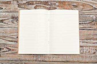 Livro de papel reciclado no fundo de madeira.
