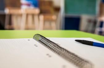 Livro de recortes em branco com escola e material de escritório na mesa do escritório