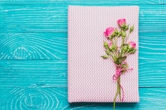 Livro e flores na superfície de madeira