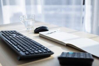Local de trabalho com teclado, mouse, calculadora e caneta