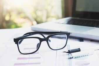 Local de trabalho no escritório com laptop e óculos em mesa de madeira.