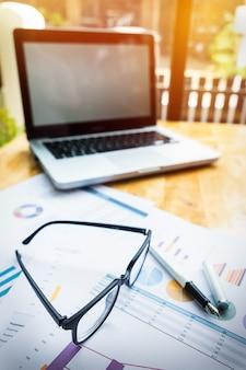 Local de trabalho no escritório com laptop e óculos na mesa de madeira