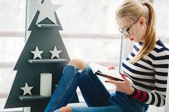Loura, senhora, pretas, óculos, lê, livro, sentando, antes, madeira, Natal, árvore, sacada