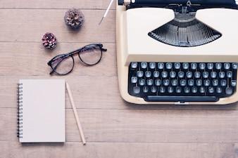 Lousa creativa plana de mesa de trabalho vintage com máquina de escrever, óculos e caderno, mesa de madeira de textura