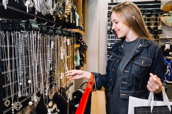 Lovely girl explorando acessórios na loja