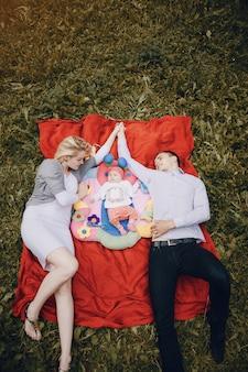 Loving casal deitado sobre o lado do seu bebê