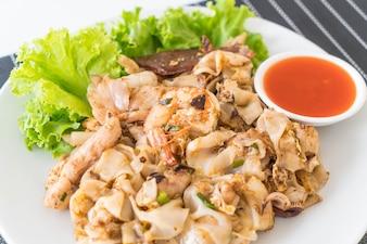 Macarrão de farinha de arroz fresco agitado com carne mista e ovo