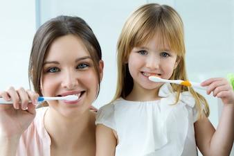 Mãe e filha escovando dentes no banheiro