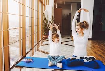 Mãe e filha fazendo yoga