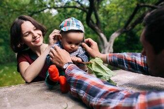 Mãe e pai colocando boné na criança