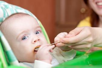 Mãe filha de alimentação com colher