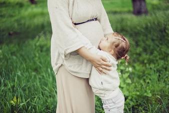 Mãe grávida abraçando seu filho