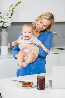 Mãe segurando seu bebê na cozinha