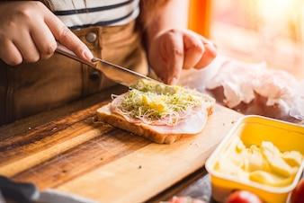 Manteiga de espalhamento em um sanduíche
