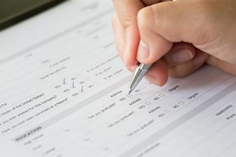 Mão com a pena sobre caixas de seleção em branco no formulário de candidatura