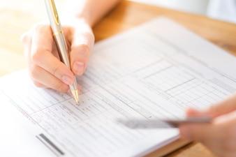 Mão com caneta e cartão de crédito sobre o formulário de inscrição.