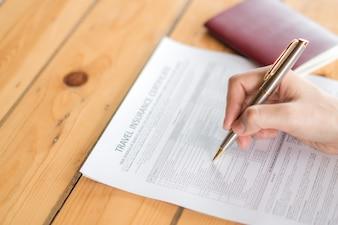 Mão com caneta sobre o formulário de inscrição do seguro de aviação de viagem e passaporte.