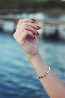 Mão com unhas pintadas e uma pulseira