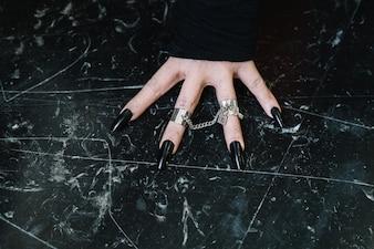 Mão com unhas pretas